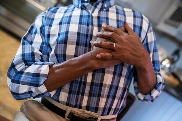 man holding is chest caused by hypertension